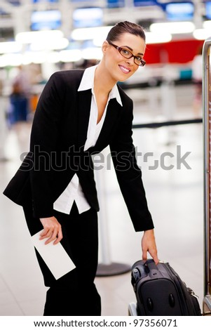 Businesswoman checking size of her carry-on luggage at airport - stock photo