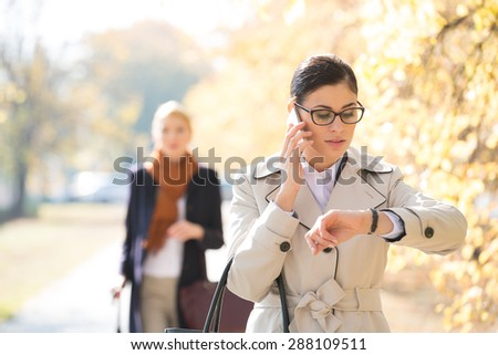 Businesswoman checking time while colleague standing in background at park - stock photo