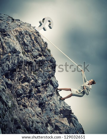 businesswoman climbing mountain hanging on rope pound on top