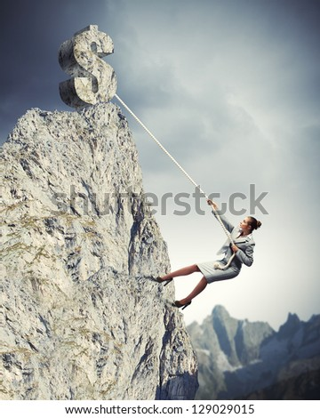 businesswoman climbing mountain with dollar on top - stock photo