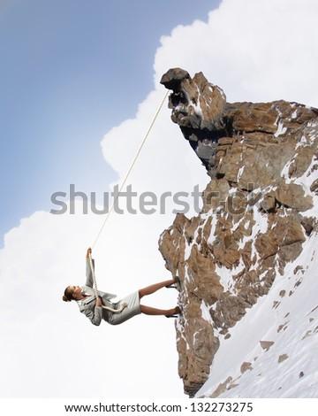 businesswoman climbing snowy steep mountain hanging on rope - stock photo