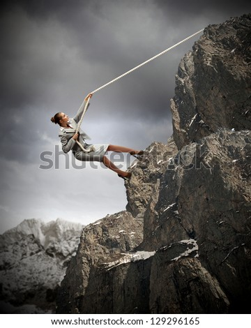 businesswoman climbing steep mountain hanging on rope