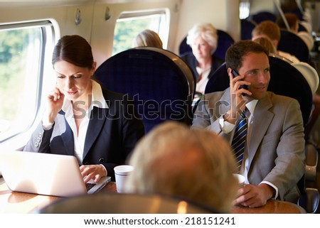Businesswoman Commuting To Work On Train And Using Laptop - stock photo