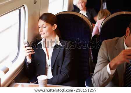 Businesswoman Commuting To Work On Train Using Mobile Phone - stock photo