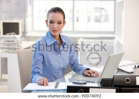 Businesswoman concentrating on work, looking at document, sitting at desk with laptop computer.? - stock photo