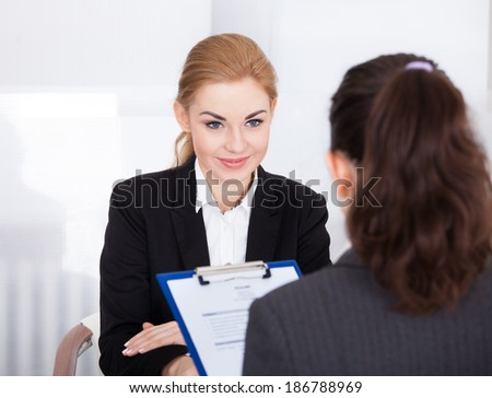 Businesswoman Conducting An Employment Interview With Young Female Applicant - stock photo