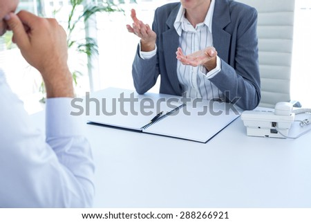 Businesswoman conducting an interview with businessman in an office - stock photo
