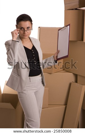 businesswoman correcting glasses keeping clipboard, carton  boxes in background