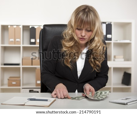 Businesswoman counting out money at her desk setting aside banknotes to cover debts and expenditure