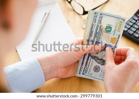 Businesswoman counts US dollar banknotes next to a paper notebook and a calculator.