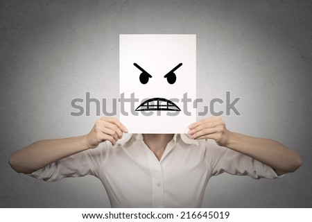 businesswoman covering her face with angry mask isolated grey wall background. Negative emotions, feelings, expressions, body language - stock photo