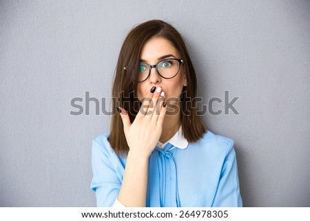 Businesswoman covering her mouth with her hands. Wearing in blue shirt and glasses. standing over gray background. Looking at camera - stock photo