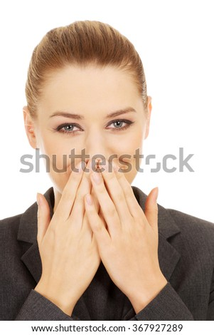 Businesswoman covering mouth with hands. - stock photo