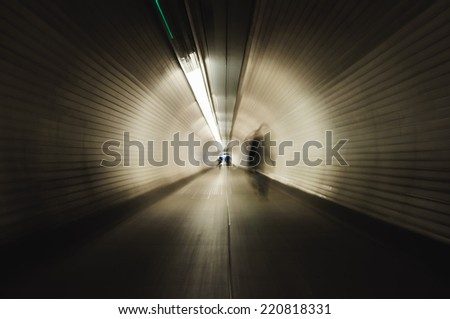 Businesswoman crossing a tunnel in London. Image with blur zoom effect - stock photo