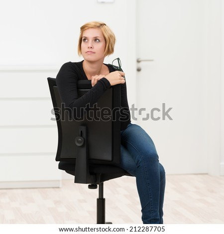 Businesswoman deep in contemplation sitting in her office chair with her glasses in her hand staring off into the distance with a thoughtful expression - stock photo