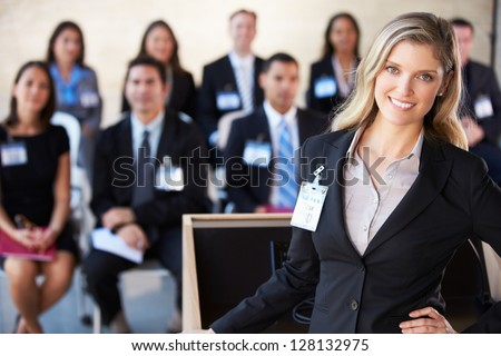 Businesswoman Delivering Presentation At Conference - stock photo