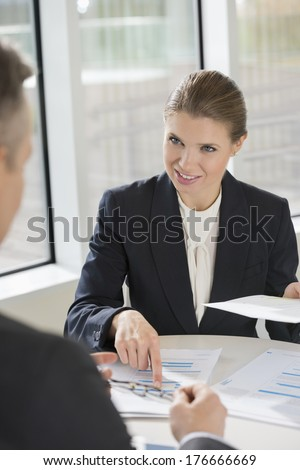 Businesswoman discussing with colleague at cafeteria - stock photo
