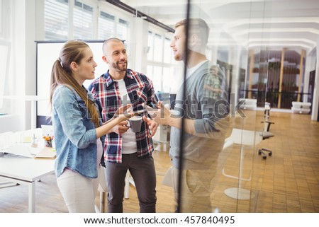 Businesswoman discussing with colleagues in creative office - stock photo