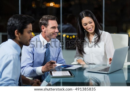 Businesswoman discussing with colleagues over laptop in office