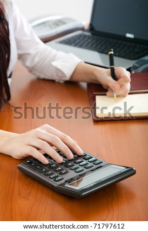 Businesswoman doing some paperwork at her desk using a calculator - stock photo