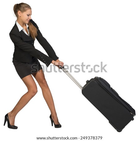 Businesswoman dragging heavy wheeled suitcase with both hands. Isolated over white background