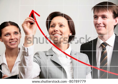 Businesswoman drawing a graph on a glass window in an office - stock photo
