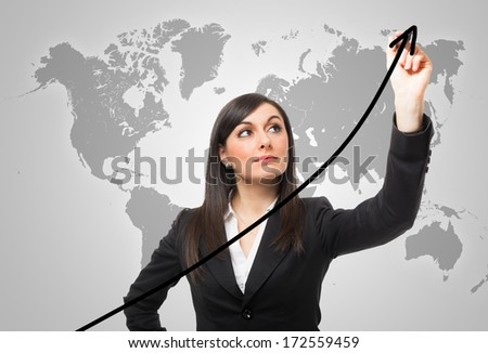 Businesswoman drawing a rising arrow, representing business growth - stock photo