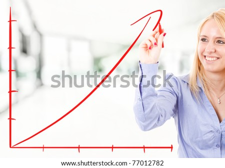 Businesswoman drawing a rising arrow, representing business growth. - stock photo