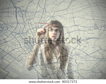 Businesswoman drawing a route on a city map - stock photo