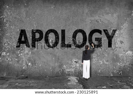 businesswoman drawing apology on the wall