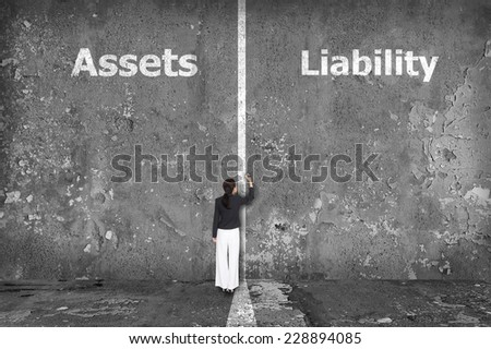 Businesswoman drawing Assets and liability on the wall - stock photo