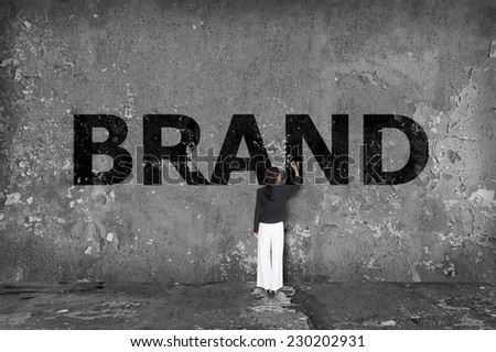 businesswoman drawing brand on the wall