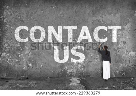 businesswoman drawing contact us on the wall - stock photo