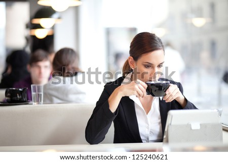 Businesswoman drinking coffee / tea and using tablet computer in a coffee shop - stock photo