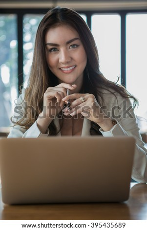 Businesswoman drinking coffee / tea and using tablet computer in a coffee shop