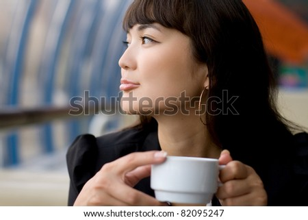 Businesswoman drinking tea in a cafe - stock photo
