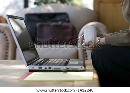 Businesswoman drinks morning coffee and thinks while working at a business travel hotel (focus point on the cup of coffee and pen). - stock photo