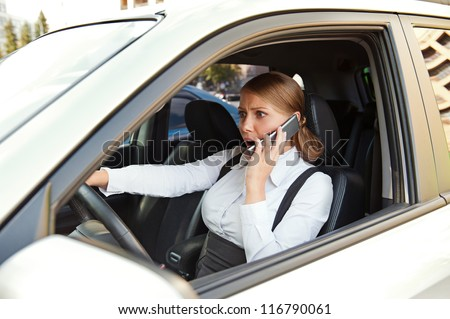 businesswoman driving the car and angrily talking on the phone - stock photo