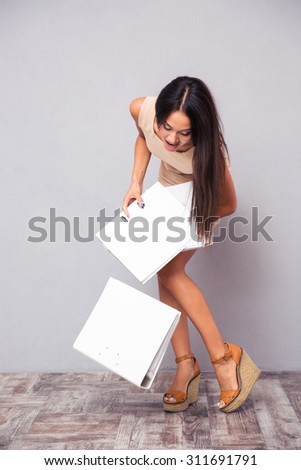 Businesswoman dropping folders on the floor over gray background - stock photo