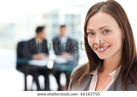 Businesswoman during a meeting with two businessmen sitting in the background