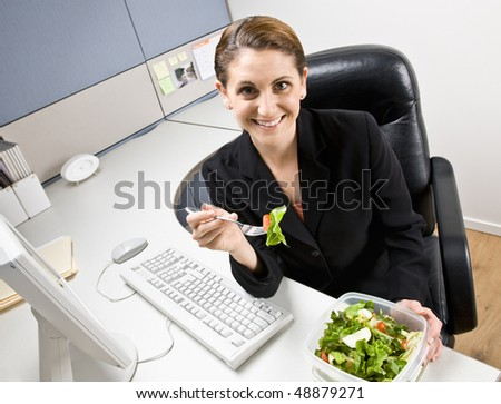 Businesswoman eating salad at desk - stock photo