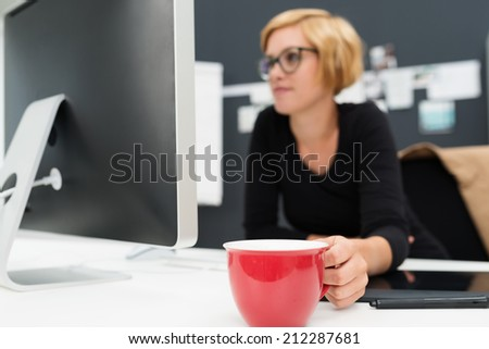 Businesswoman enjoying a coffee break sitting at her desk holding a large red cup in her hand with focus to the cup - stock photo