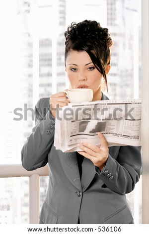 Businesswoman enjoys coffee and newspaper