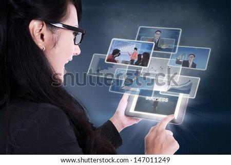 Businesswoman excited looking at success pictures on electronic tablet - stock photo
