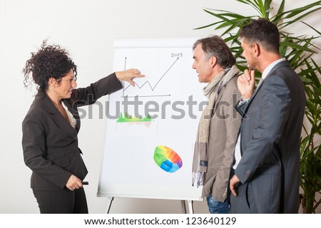 Businesswoman Explaining Charts to Her Male Colleagues - stock photo