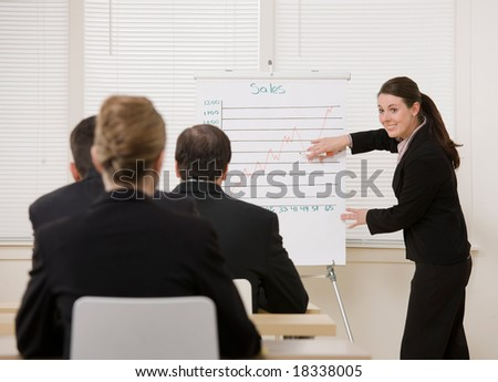 Businesswoman explaining presentation of financial line graph to co-workers - stock photo