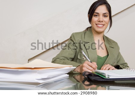 Businesswoman filing out paperwork at desk.