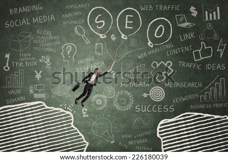 Businesswoman flying with balloon in classroom through gap on the blackboard - stock photo