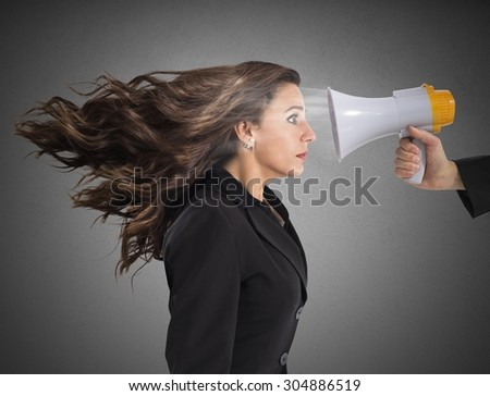 Businesswoman frightened by the megaphone loud noise - stock photo