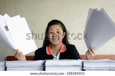 businesswoman frustrated and raise up papers into the air at a table with pile of papers - stock photo